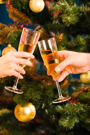The glasses of champagne making a clink on the background of christmas- tree photo