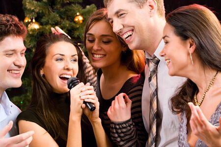 Retrato de varias personas cantando una canción junto a un karaoke partido  Foto de archivo - 2644772
