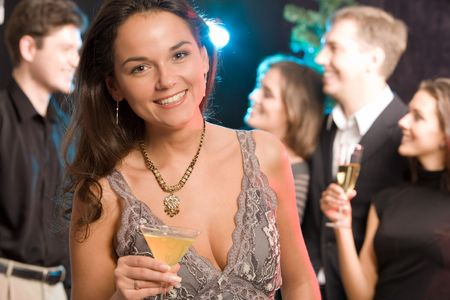 Portrait of charming woman holding her cocktail on the background of people  photo