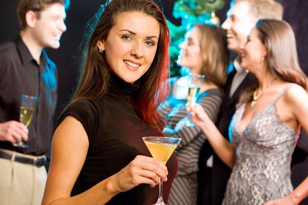 Attractive woman enjoying a cocktail while a party photo