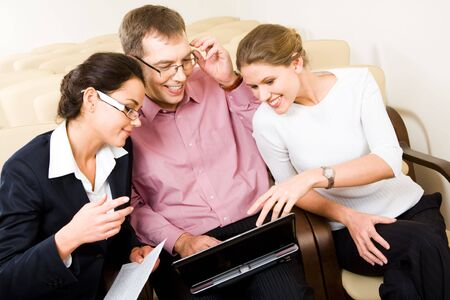 Image of three business people sitting in the armchairs and having a conversation during business meeting looking into the laptop screen photo