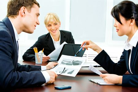 Portrait of business partners holding business documents and discussing them while their colleague looking at them with smile photo