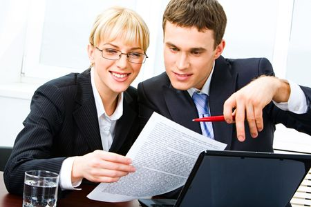 Portrait of two business partners sitting at the table and working together in the office on the background of window photo