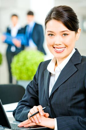 Portrait of smiling business woman sitting at the table  photo