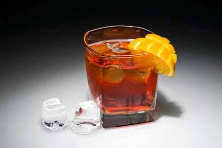 Negroni cocktail with ice and piece of orange on the black background photo