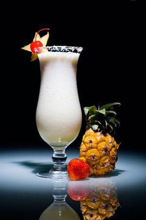 Pina Colada cocktail with cherry surrounded by pineapple and strawberry photo