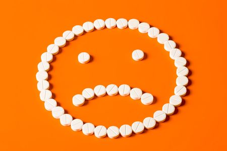 pained: Pained face made up out of white tablets on the orange background