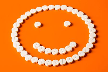 Smiling face made up out of white tablets on the orange background photo