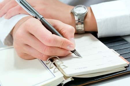 A businessman makes note in the notepad Stock Photo - 2657525