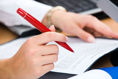 Close-up of female hand holding the red pen  Stock Photo - 2657524