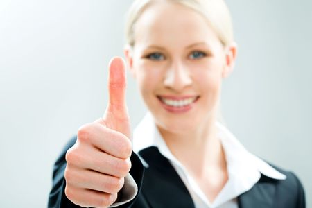 Image of business woman giving the thumbs-up sign photo