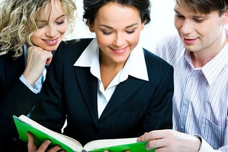 Group of three mature students reading a book together photo