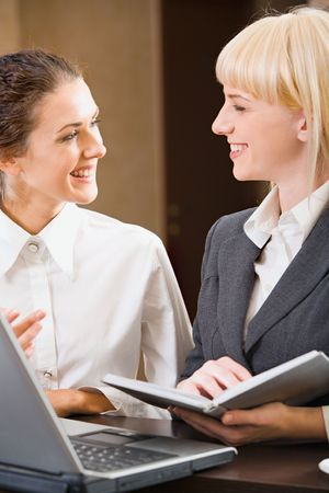 Two contemporary smiling businesswomen are chatting  photo