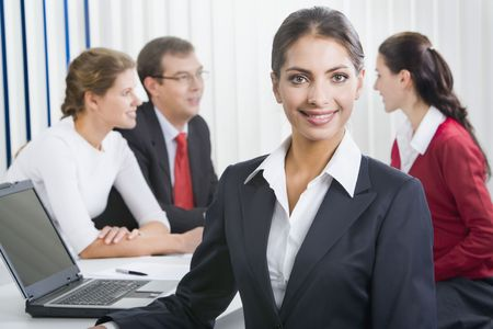 Portrait of a confident woman with her business team on the background photo