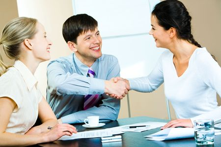 agreeing: Image of business partners shaking hands at business meeting with a smiling businesswoman sitting near by  Stock Photo