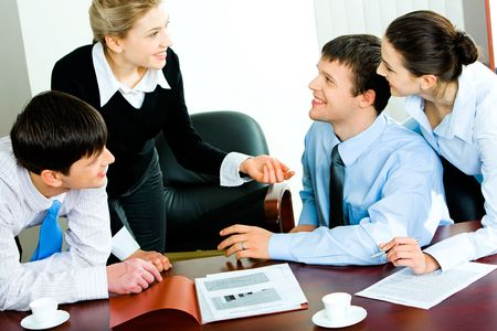Business lady explaining her working idea to group of three businesspeople listening to her with friendly smiles in the office  photo