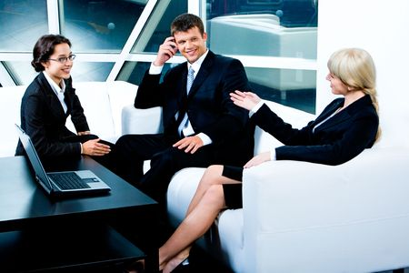 woman speaking: Image of three business partners sitting on white sofa near the table with open laptop on it and discussing their business ideas