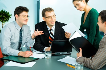 Portrait of businessmen sitting at the table and discussing business plans with an elegant businesswoman with a document standing near by Stock Photo - 2709736