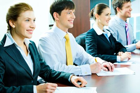 Portrait of students sitting at the table in row at seminar