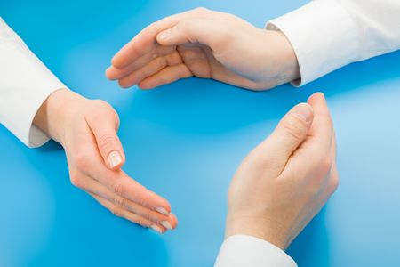 Human hands making symbolic circle on a blue background photo