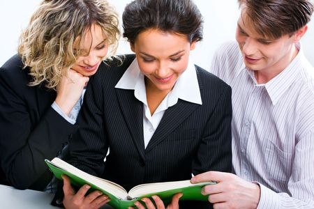 Image of business people reading the book which the woman holding  Imagens