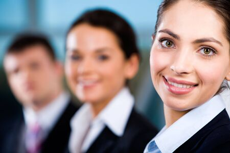 Line of business people's faces with beautiful woman in front  Stock Photo