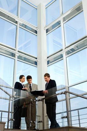 Image of business people interacting on the background of large window photo