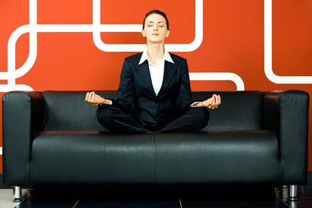Portrait of business woman meditating on the sofa in the room  photo