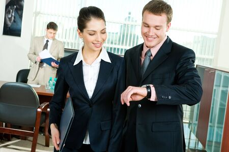 Portrait of man and woman looking at watch on businessman�s hand meaning to hurry up to work on the background of serious working man Stock Photo - 2738341