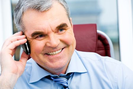 Portrait of a smiling senior businessman speaking on the cellular phone Stock Photo - 2752197