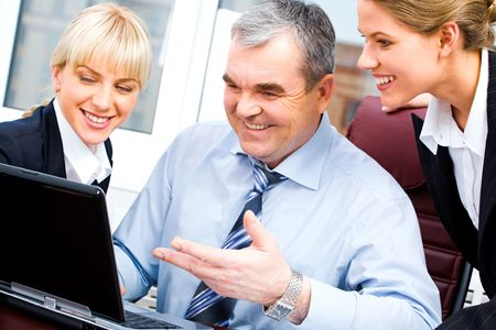 Portrait of senior boss and two young businesswomen looking at the laptop monitor with smiles on the background of office window Stock Photo - 2752212