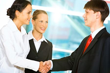 Photo of two business partners shaking hands after signing contract in the office with their colleague near by photo