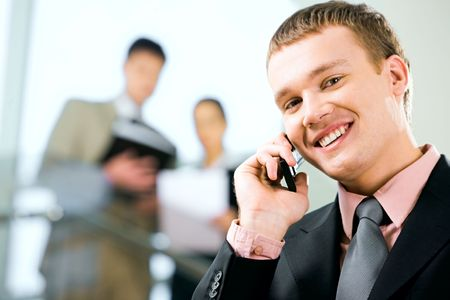 Portrait of a young handsome businessman speaking on the phone and looking at camera with smile in working environment Stock Photo - 2752195
