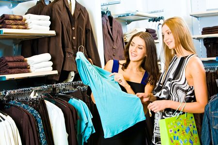 青いドレスを保持し、それを見て笑顔でさまざまな服の背景に衣料品店で 2 人の女の子の写真