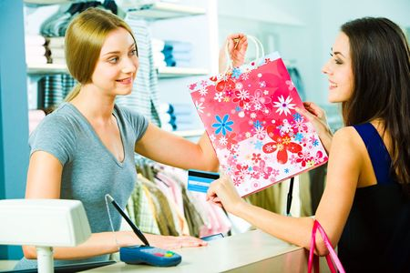 Photo of a friendly salesperson giving shopping bag to pretty customer in the mall with smile photo