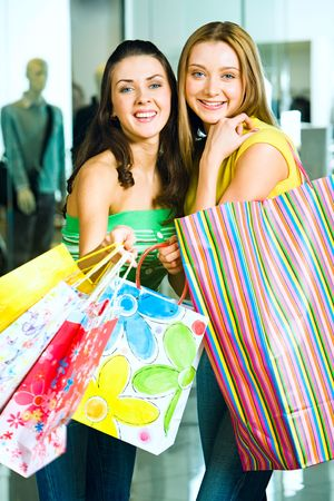 Vertical image of two pretty friends with shopping bags looking at camera with smiles on the background of shop window photo