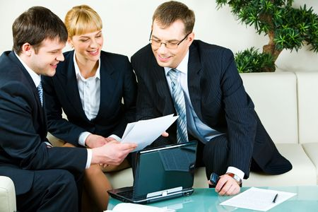 Two businessmen and businesswoman looking at document at meeting in the room  photo