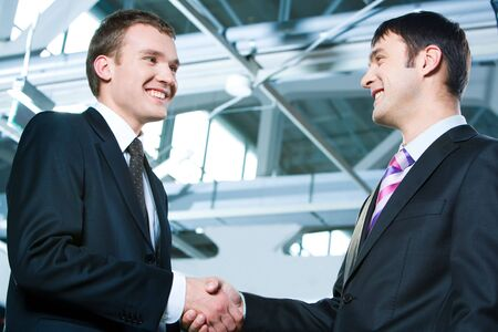 Portrait of two confident business men shaking hands at meeting  photo