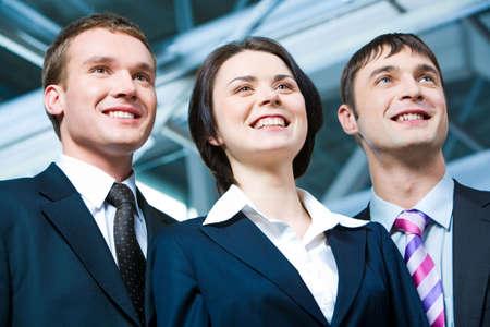 Portrait of business woman between two confident men   photo