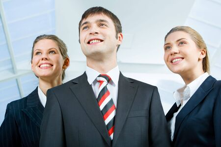 Image of three business people in suits and smiling  photo
