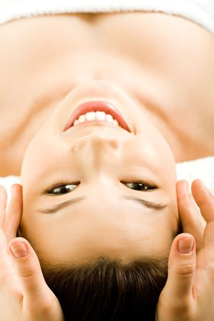 Vertical image of beautiful girl smiling and looking at camera while a facial massage Stock Photo - 2779520