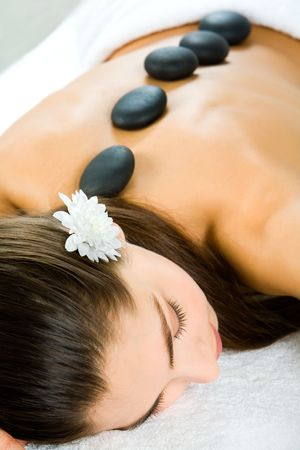 stones with flower: Attractive woman getting a stone massage in a spa Stock Photo