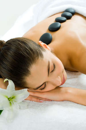 Image of a pretty girl lying in the beauty salon with closed eyes and enjoying spa procedure with madonna lily by her head photo