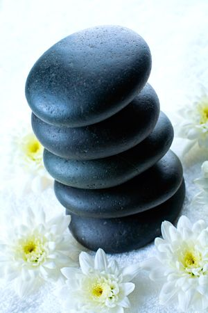 Heap of black spa stones placed on towel with the white flowers photo