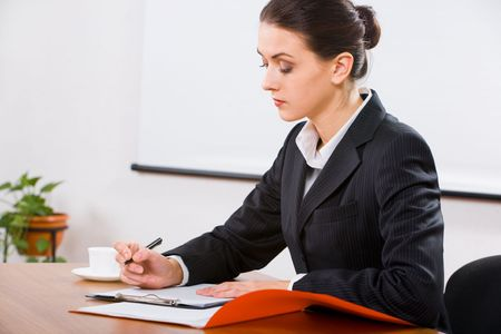 Image of business woman sitting at the table with documents, paper and cup on it  photo
