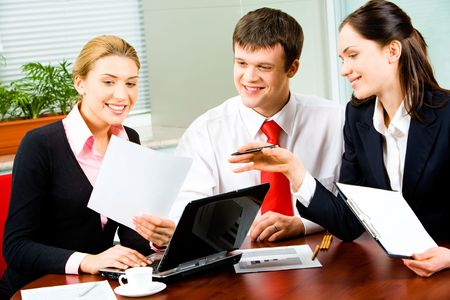 Portrait of three businesspeople working at the table in the office looking into document in woman's hand Stock Photo - 2836813