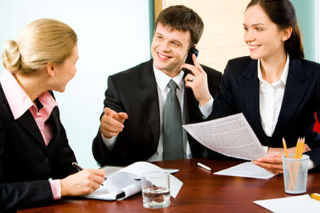 Portrait of business man telling something to colleague while calling on the phone with woman sitting near by  photo