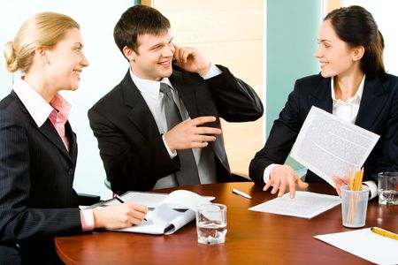 Portrait of three business people interacting with each other in a working environment   photo