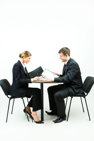 working place: Image of two business people in suit sitting at the table on a white background