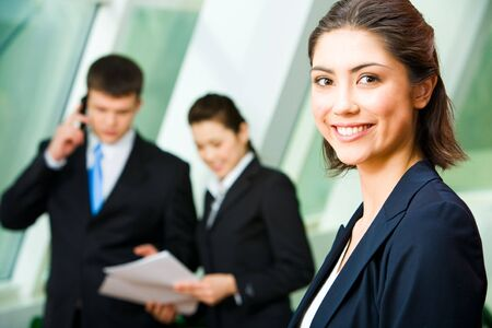 Face of pretty professional with charming smile on the background of colleagues   photo